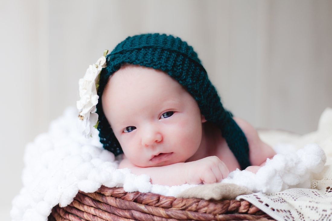 Newborn baby girl in Lutz looks into camera while wearing an emerald green knit outfit