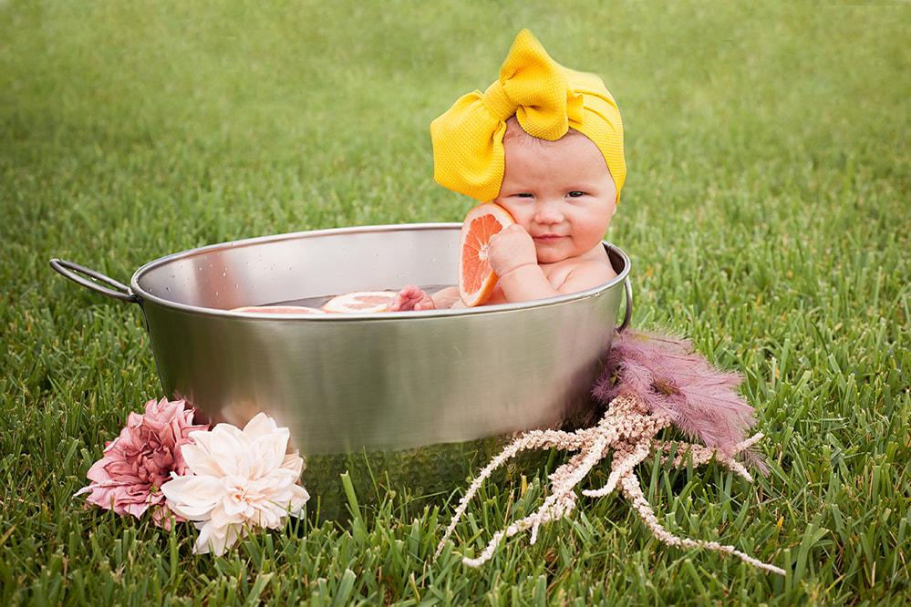 Baby girl in metal basin with flowers and citrus slices in Tampa FL