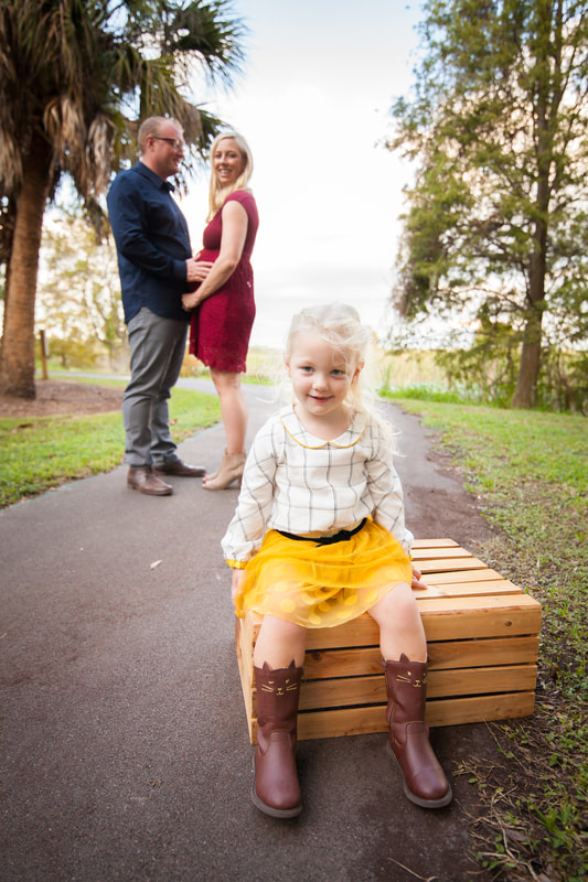 Smiling little girl about to become a big sister sits with her parents behind her