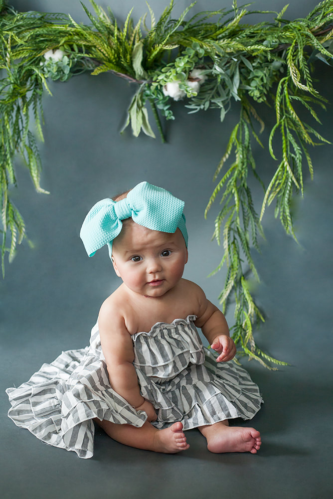 baby girl on a dark gray background with foliage all around her in gray and white dress
