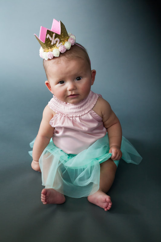 Six month old baby girl wearing 1/2 birthday crown on gray/blue background