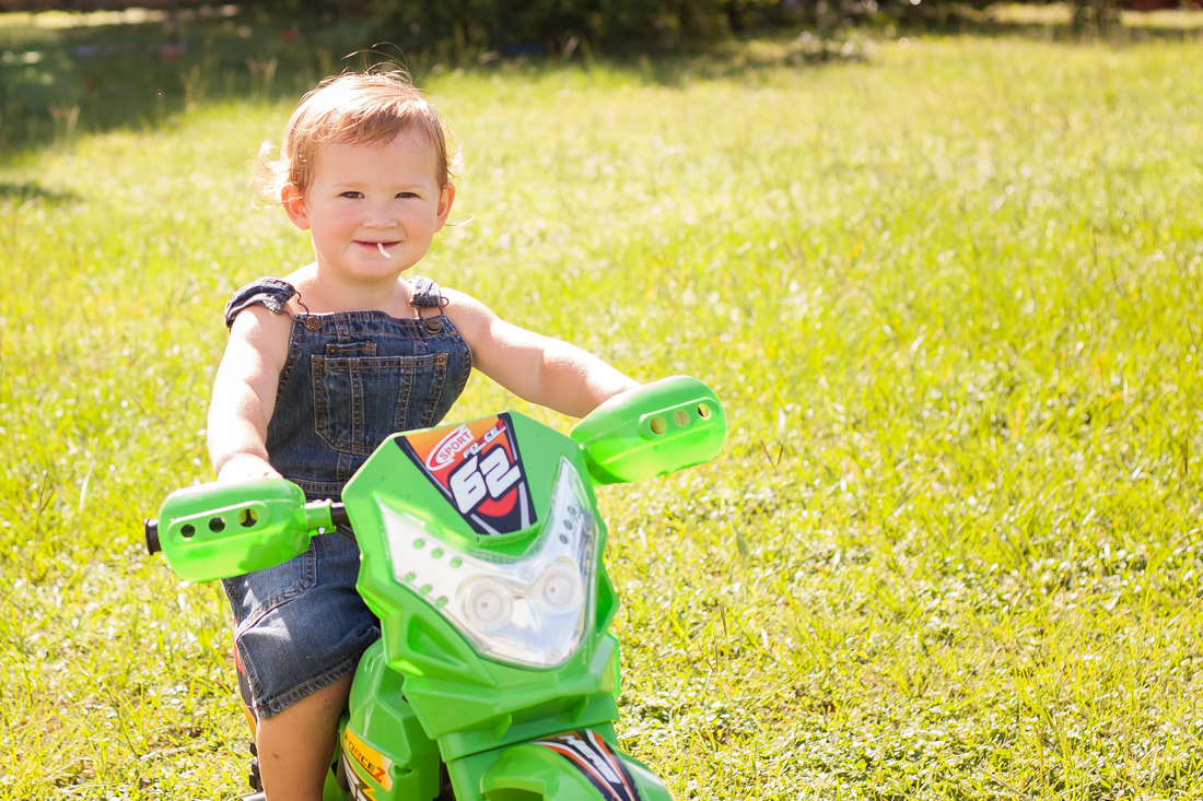 Toddler Boy sits on dirt bike in beautiful sun drenched field in Temple Terrace