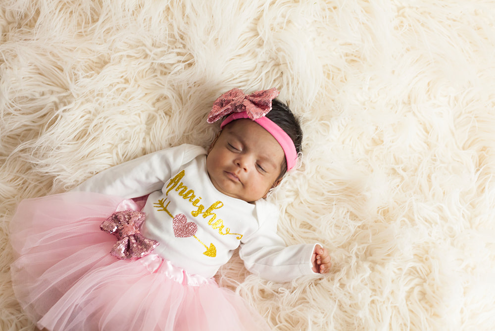 baby girl in tutu sleeps on a white fur blanket