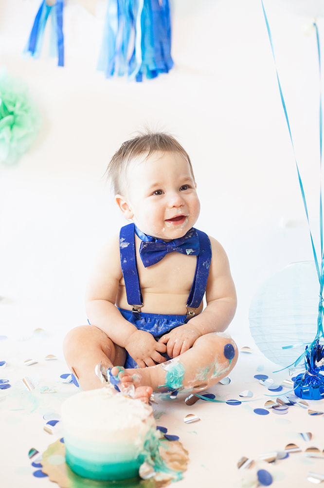 Smiling baby boy smashing a blue and white cake