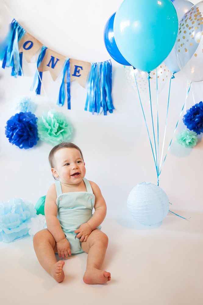 Sweet smiling baby in front of a banner that reads