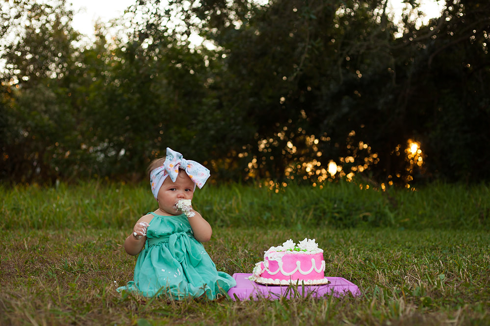 Baby girl eating a big handful of cake