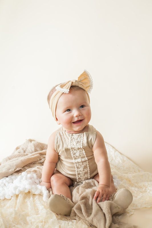 Smiling baby girl photo in off white romper on an off white background
