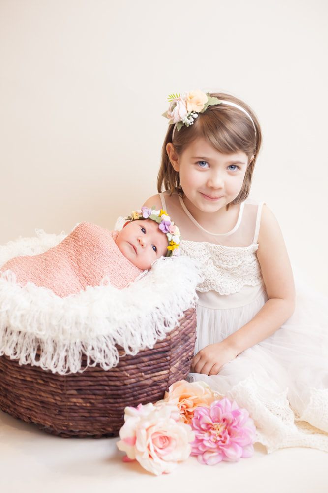 Big sister smiles next to newborn baby in a basket on a white background. Taken in Tampa, FL