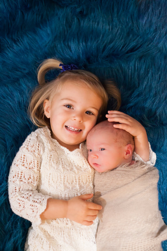 a toddler in a white dress lies on blue fur snuggling her newborn baby brother
