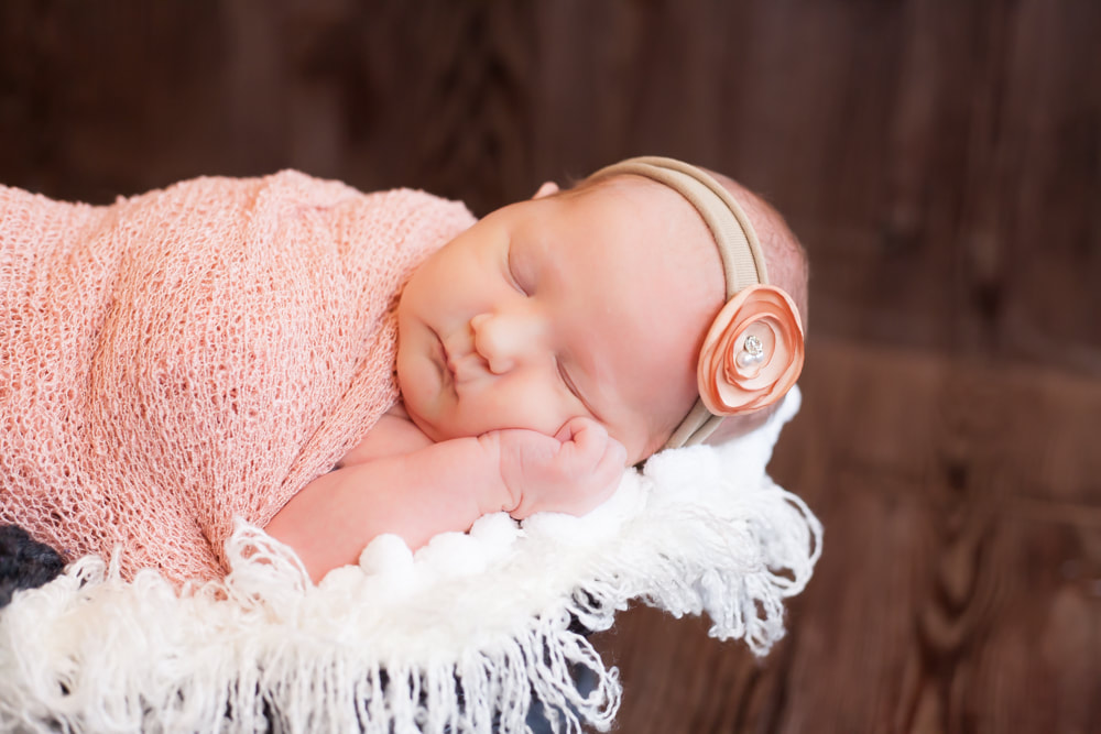 newborn baby sleeping on her side in soft blankets with a dark wood background