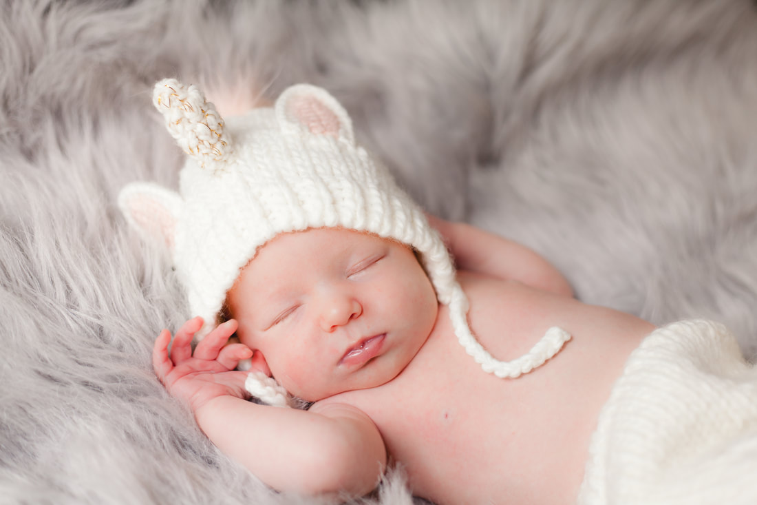 newborn baby girl wearing a unicorn outfit sleeps with her hands up near her face