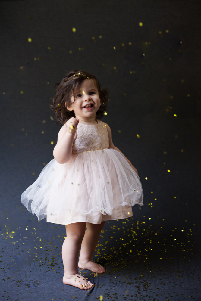 Standing baby smiles at the camera as confetti falls around her