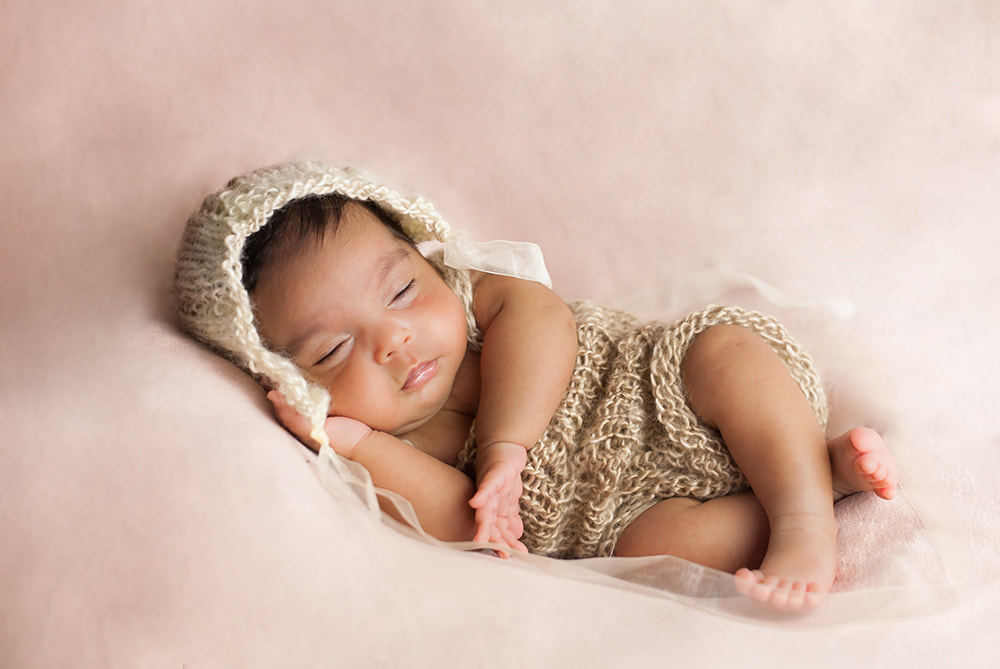 sleeping baby in side lying pose with a brown and pink color scheme