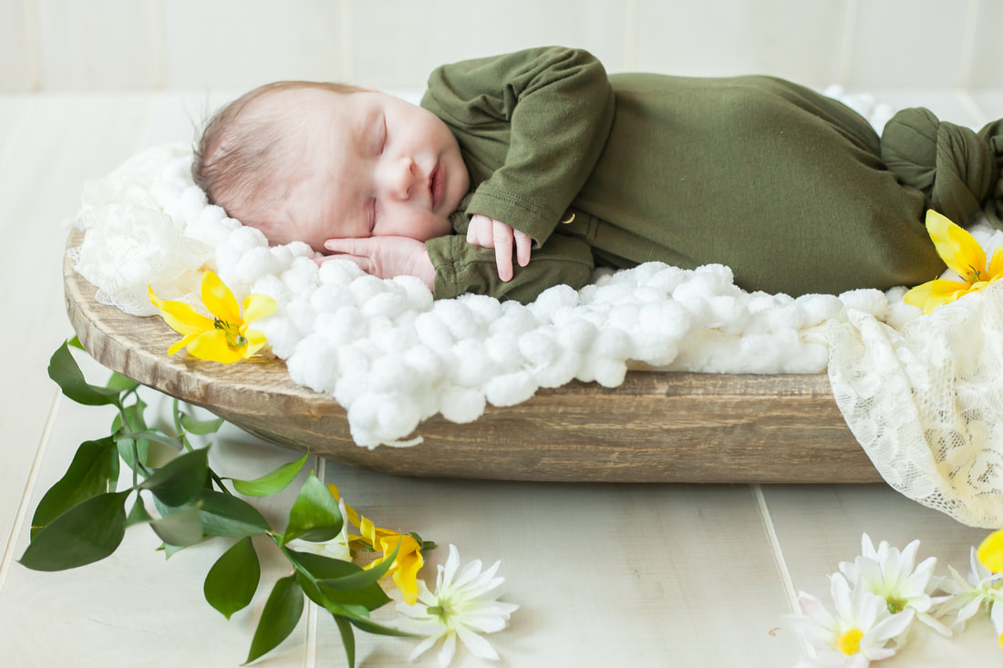 baby in green sleeps on her side in a wooden bowl surrounded by flowers and greenery